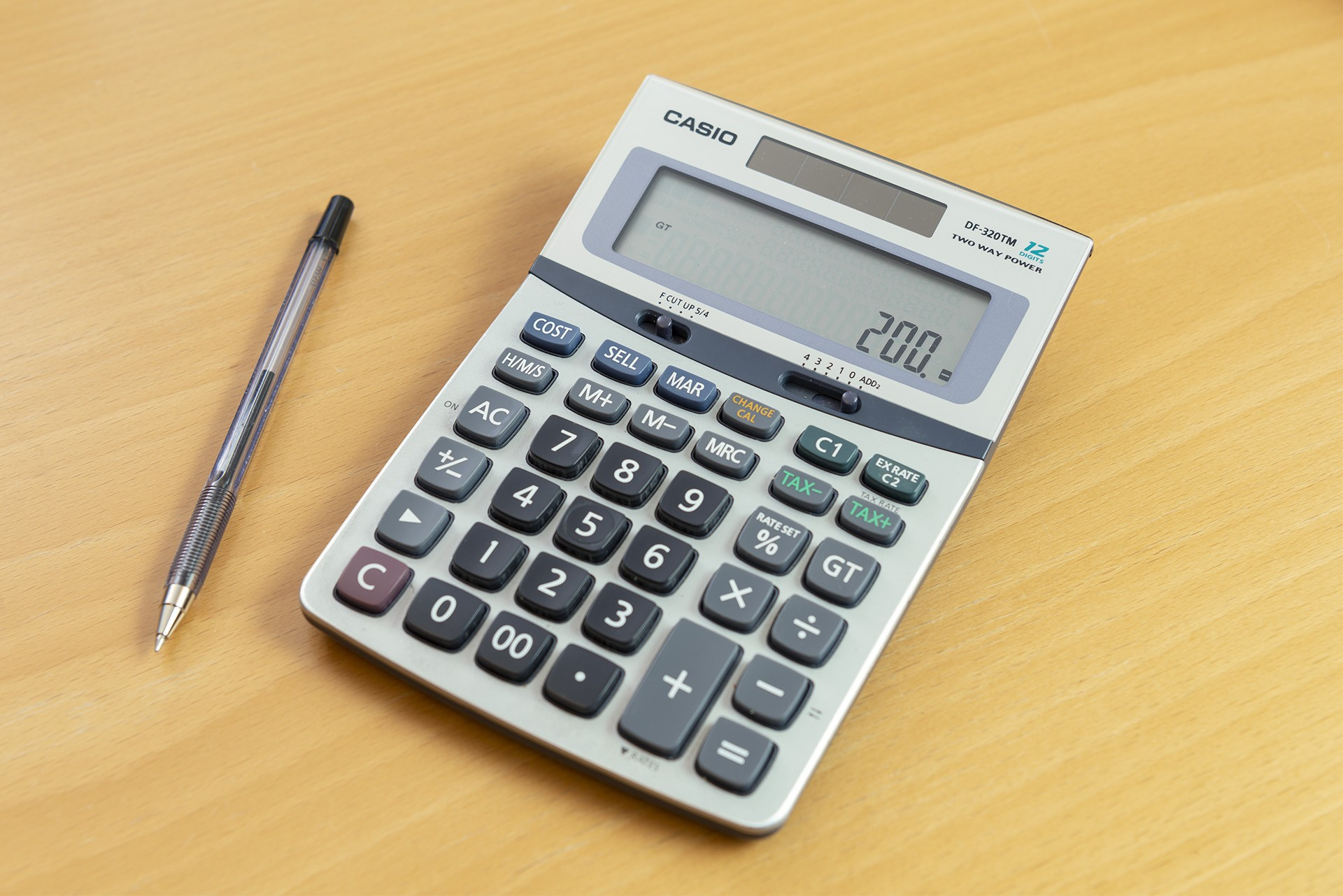Kuvassa laskin ja kynä